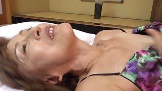 Mature Japanese Asano TAeko spreads her legs and drills her holes